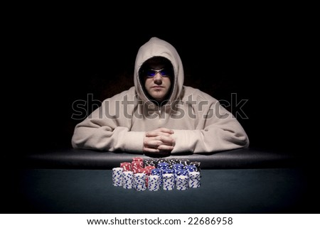 a poker player sitting at a table trying to hide his expressions - stock photo