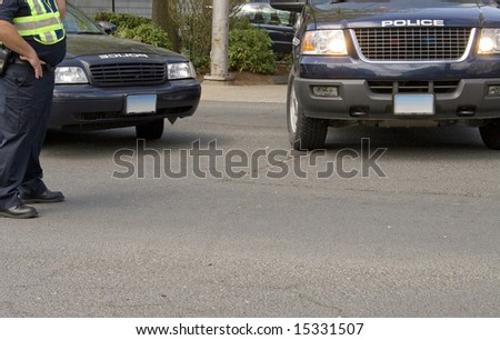 A police background with two vehicles and an officer at work.  Plenty of copy space in the street. - stock photo