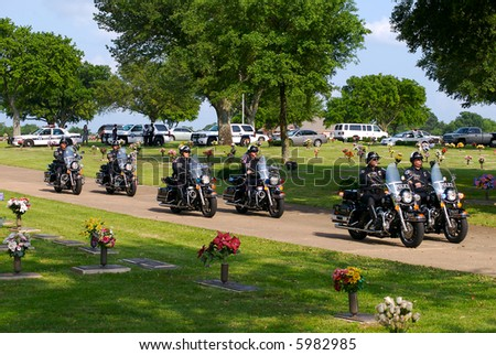 A police motorcade at the funeral of a slain deputy.