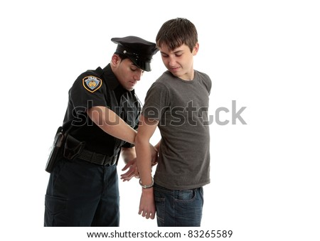 A police officer arrests and handcuffs a young male teen felon. - stock photo