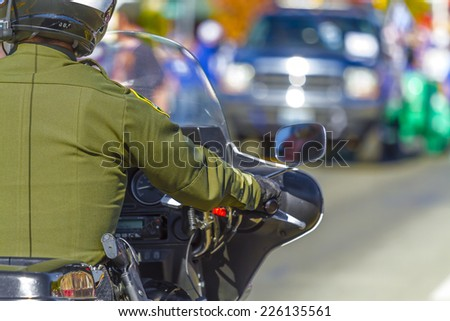 A police officer on a motorcycle driving in traffic. - stock photo