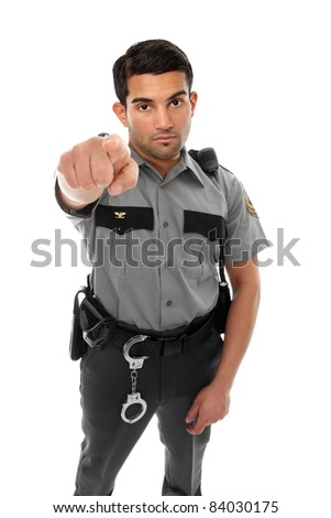 A police officer, prison guard or similar uniformed man stands firm with pointed finger.  Concept - stock photo