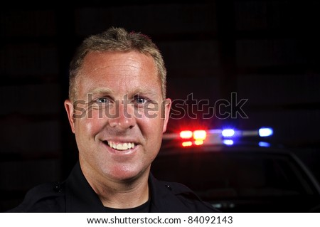 A police officer smiling in the night with his police car in the background. - stock photo