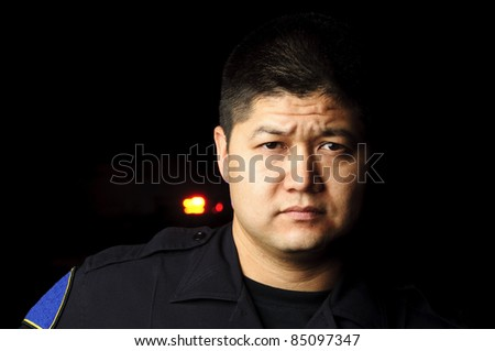 a police officer standing in the night with his patrol car in the background. - stock photo