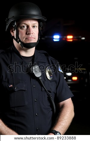 a police officer wearing a riot helmet with his patrol unit in the background.