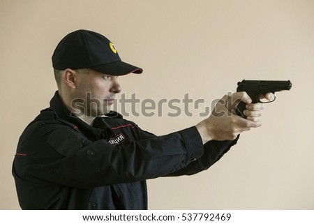 A police officer with a gun in his hand.