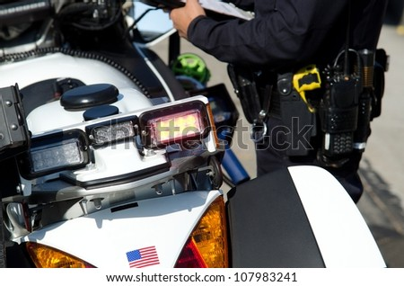 a police officer writing a ticket next to his motorcycle during his shift.
