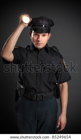 A policeman, night patrolman or security guard shining a flashlight torch to investigate or search. - stock photo