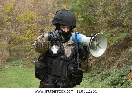 A policeman shouts orders into a megaphone