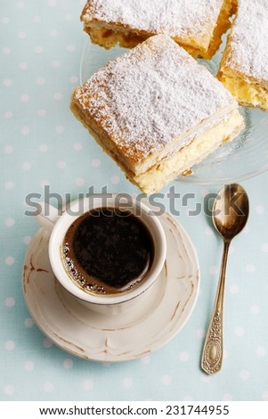 A Polish cream pie made of two layers of puff pastry, filled with whipped cream and cup of coffee. - stock photo