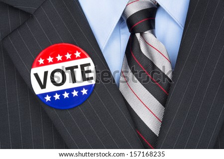A politician wearing his lapel voting pin on his elegant business suit. - stock photo