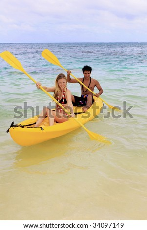 A Polynesian man and a blond caucasian girl, wearing leis, paddle their ocean kayak towards shore - stock photo