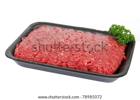 A polystyrene container of uncooked ground beef with a parsley garnish - stock photo