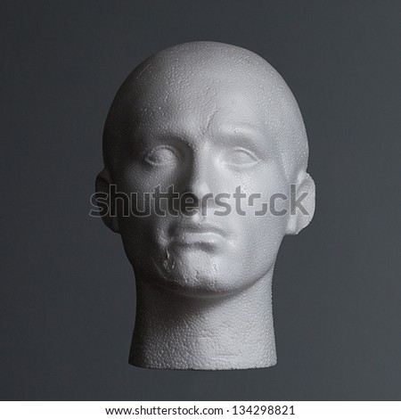 A polystyrene head on a grey background side lit. - stock photo