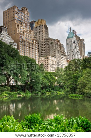 A pond in central park with high rise buildings behind it in New York City - stock photo