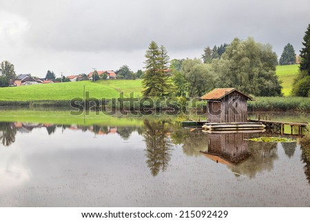 A pond with a fischer hut in the cloudy morning in a rural area in Bavaria, Germany