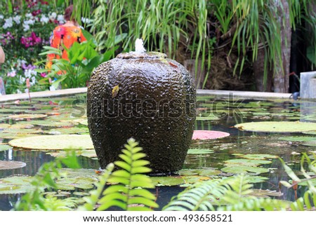 A pond with a fountain in the form of a huge jug. Green leaves lily. Tropical landscape. Thailand. Phuket.