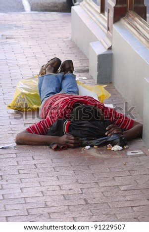 A poor beggar lying on the side of a street in the dirt in Cape Town - stock photo