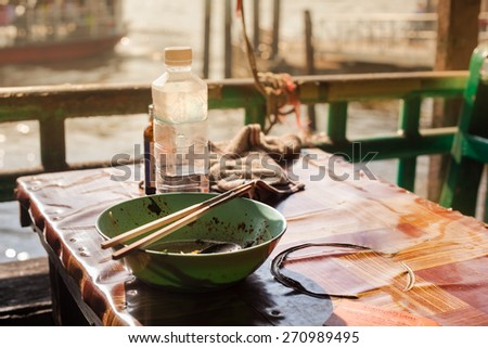 a poor consumed asian meal on a dirty table near the port - stock photo