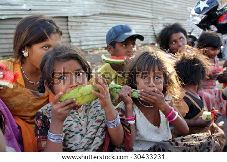 A poor girl in India eating watermelon along with her other family who spend their time begging on the streets. Focus on the eyes of the girl in front.