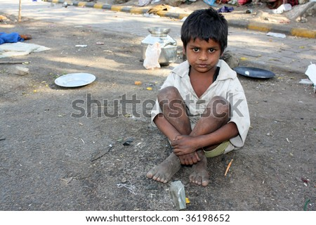 A poor kid in India, sitting on the streetside. - stock photo
