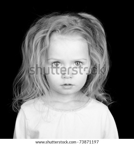 A poor missing child stares with her deep eyes at the viewer.  She is a starving child. - stock photo