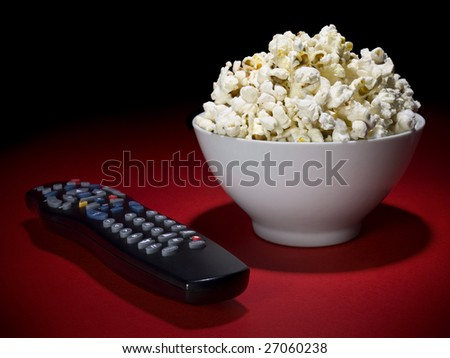 A popcorn bowl and a remote control ready for fun. - stock photo
