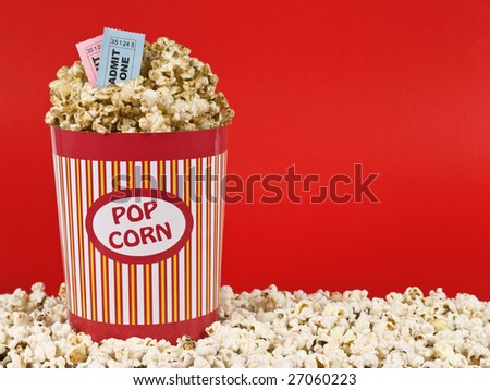 A popcorn bucket over a red background. Movie stubs sitting over the popcorn. - stock photo