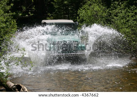 A popular vintage off-road vehicle splashes water over the top while fording a mountain stream. - stock photo