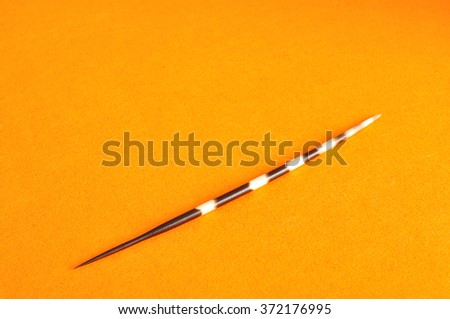 A porcupine spine isolated against a orange background - stock photo