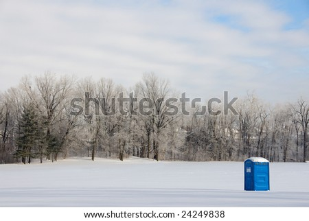 A port-a-potty sits in a remote field covered in snow - stock photo