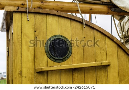 A port hole on an old wooden ship - stock photo