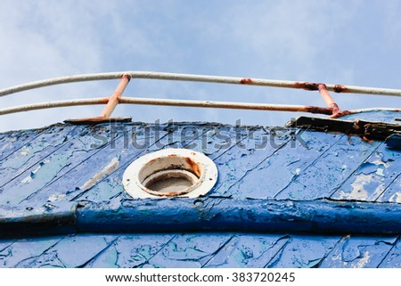 A port hole window on an old blue fishing boat - stock photo