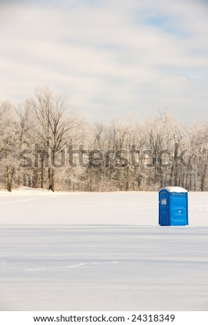 A portable restroom site in a empty snow covered field. - stock photo