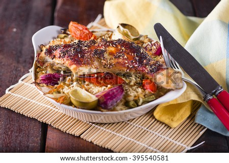 A Portion Baked chicken leg with rice and vegetables in a small white plate - stock photo