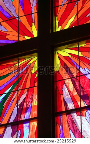 A portion of a stained glass window with wooden molding forming a Christian cross - stock photo