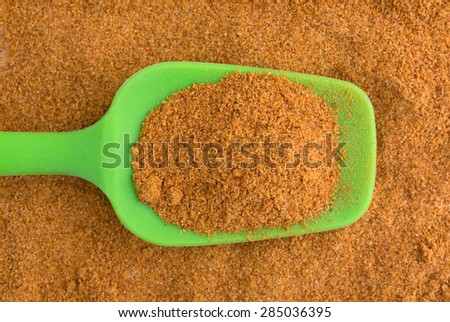 A portion of Cajun seasoning in a green spoon atop a mound of seasoning. - stock photo