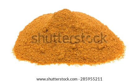 A portion of Cajun seasonings on a green spoon atop other seasonings on a white cutting board. - stock photo