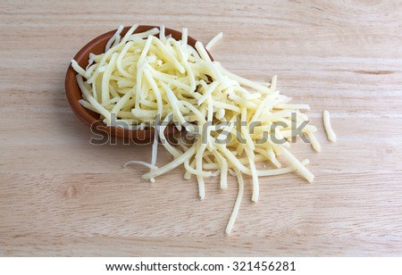 A portion of natural mild cheddar cheese spilling from a small bowl atop a wood table top illuminated with natural light. - stock photo