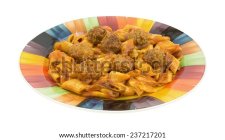 A portion of penne pasta with meatballs in a tomato sauce on a colorful plate. - stock photo