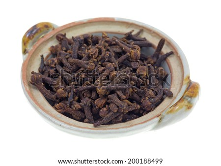 A portion of whole cloves seasoning in a small bowl on a white background.