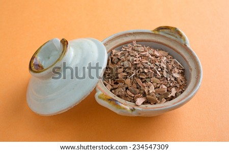 A portion of witch hazel bark in a small bowl with the lid on the side. - stock photo