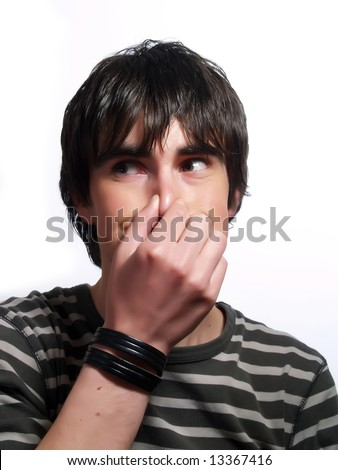 A portrait about a trendy attractive guy who is holding his nose and he is smiling. He is wearing a striped t-shirt. - stock photo