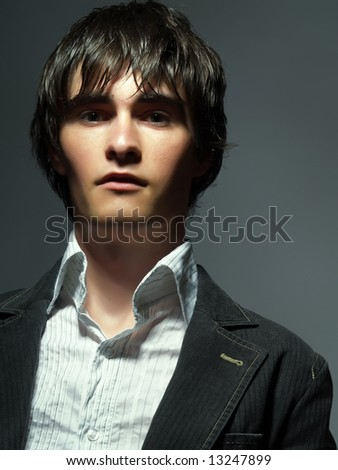 A portrait about a trendy attractive young man who has a serious and glamorous look. He is wearing a white shirt and a black suit. - stock photo