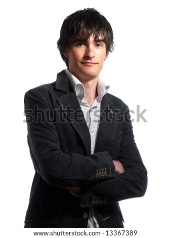 A portrait about a trendy cute guy who is smiling and he has an attractive look. He is wearing a white shirt and a stylish black suit. - stock photo