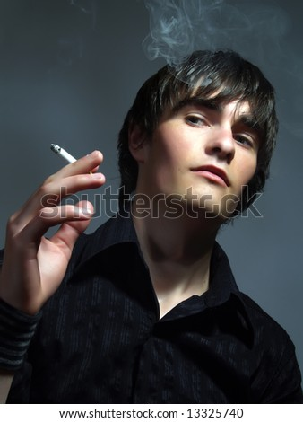 A portrait about a trendy cute guy who is smoking and he has a glamorous look. He is wearing a stylish black shirt. - stock photo