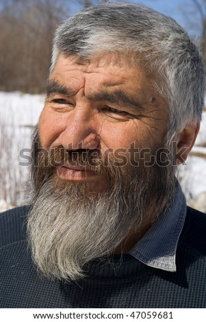 A portrait close up of the old men with grey beard. Small indigenous peope of Russian Far East.