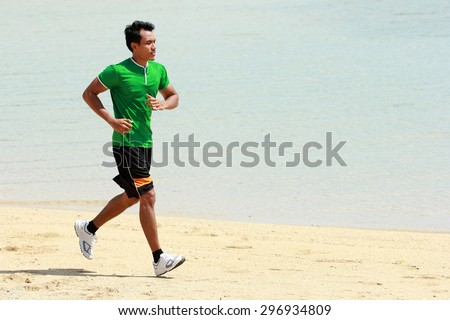 A portrait of a Asian young man running on beach, Sport concept - stock photo