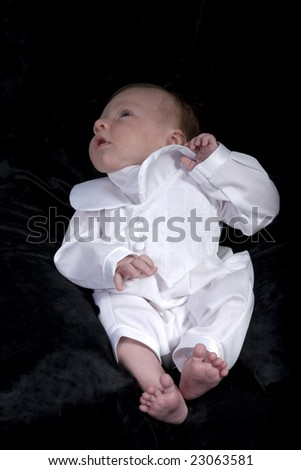 a portrait of a baby boy in a christening outfit.