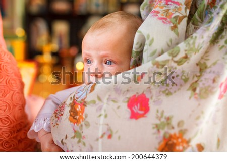 A portrait of a baby during christening ceremony on a golden background of church. This photo has a shallow depth of field and the focus is on his eye  - stock photo